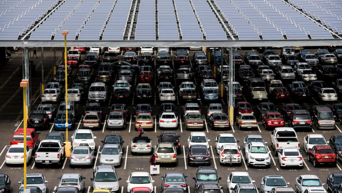 Cars parked in a parking lot under solar panels on the ASU Tempe campus.