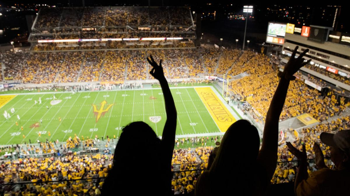 Image of two silhouettes of students making pitchfork salutes cheer at an ASU Football game. Photo by Jarod Opperman
