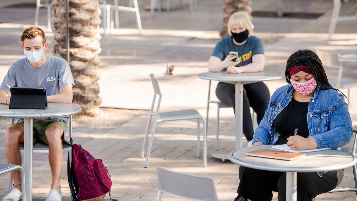 Three people sit outside at separate tables, wearing masks and working on homework or using their phones.