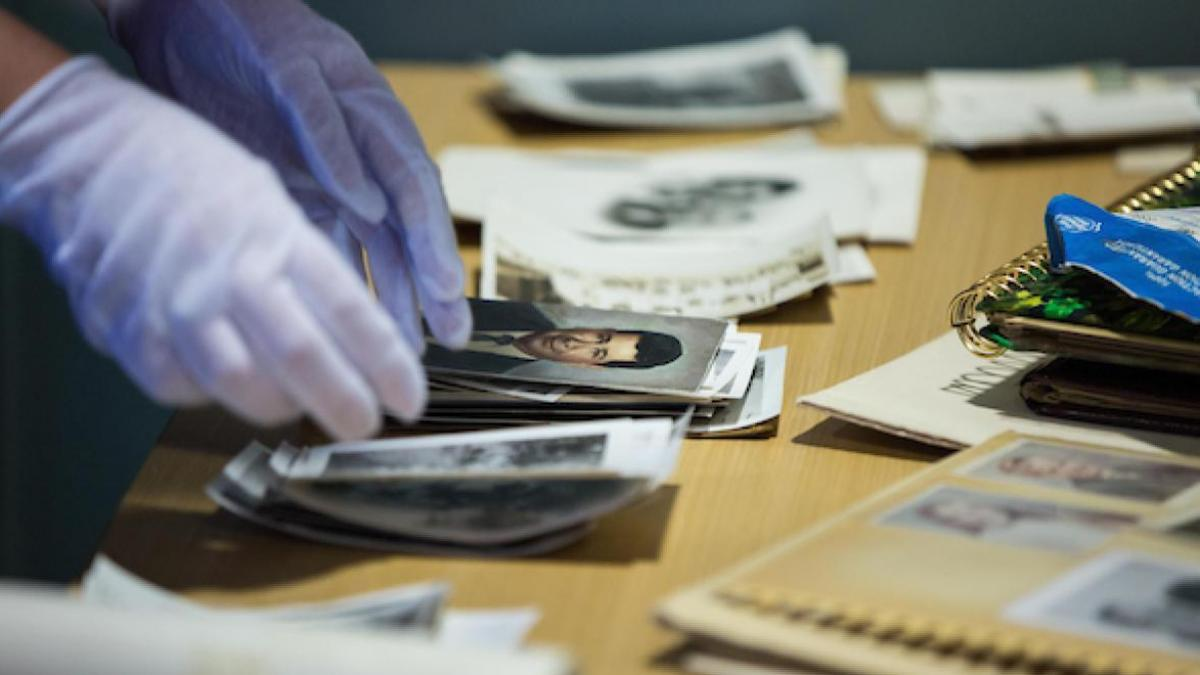 archivist wears gloves while handling photographs to scan and digitize