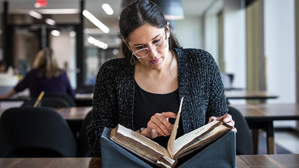 woman looking through a rare book at a table in a library reading room