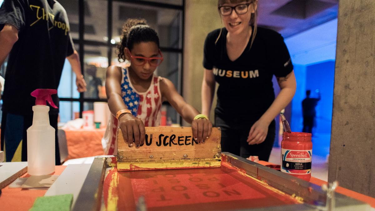 Image shows a young girl learning how to make a screenprint under the guidance of an ASU student