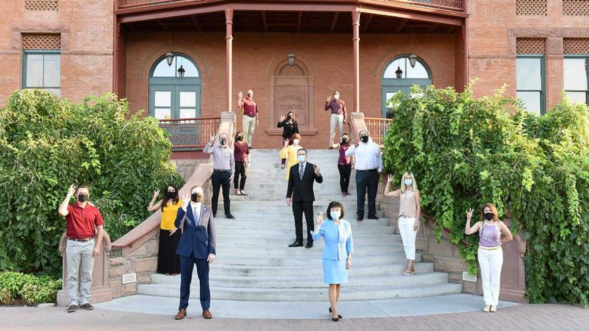 Members of the ASU Leadership Institute stand, socially distanced, on the steps of Old Main. They are wearing face masks and holding their hands in the ASU pitchfork.