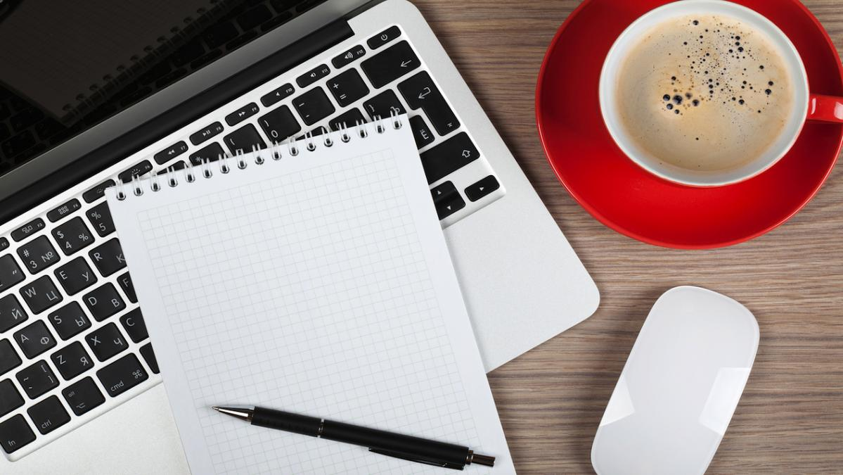 An overhead image of a laptop, an open notepad, and a mug of coffee.