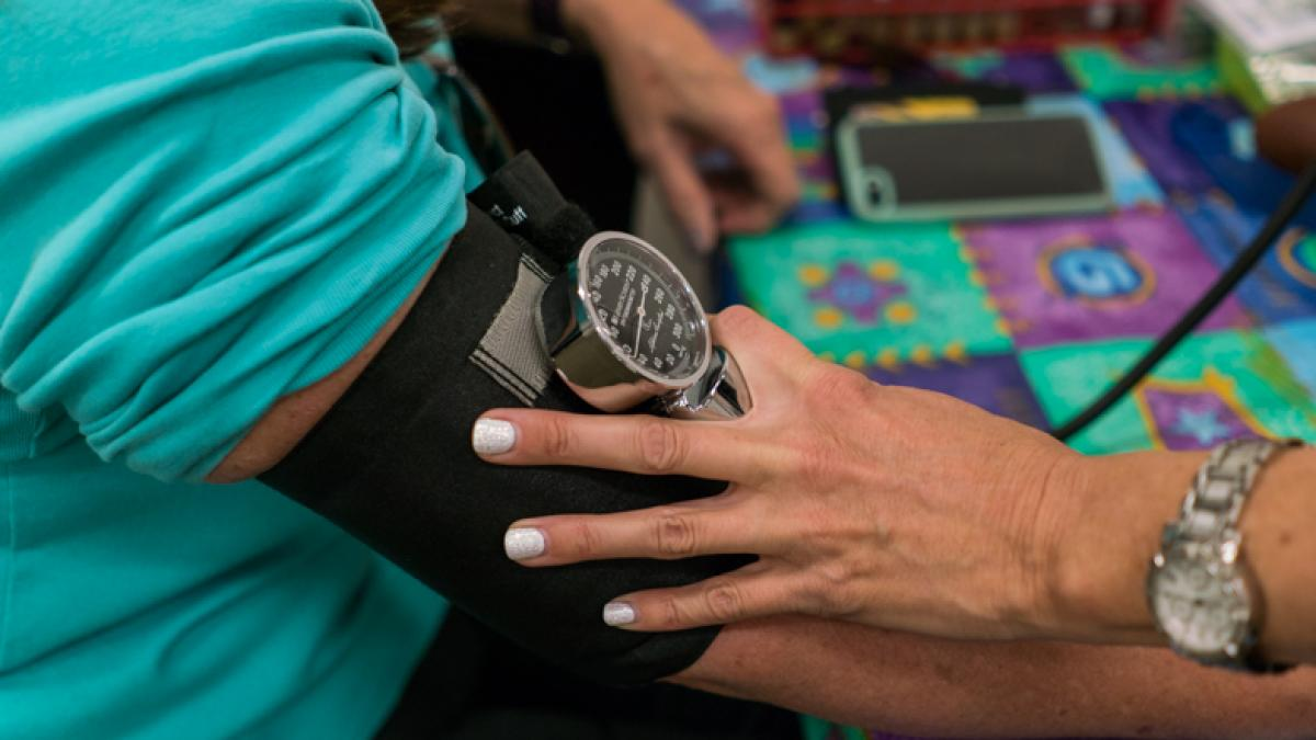 Image of a person's arm with a blood pressure cuff and gauge and another person's hand holding the cuff.