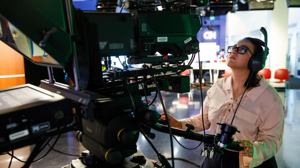 Student journalist stands behind camera in newsroom
