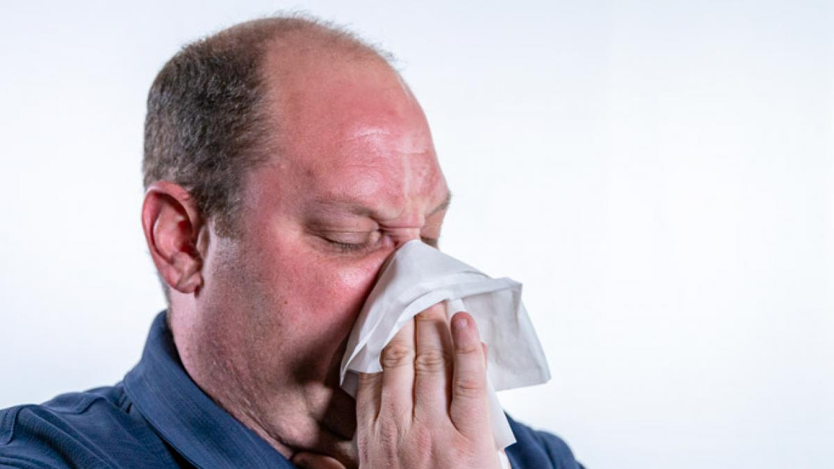 Image of a man blowing his nose into a tissue.