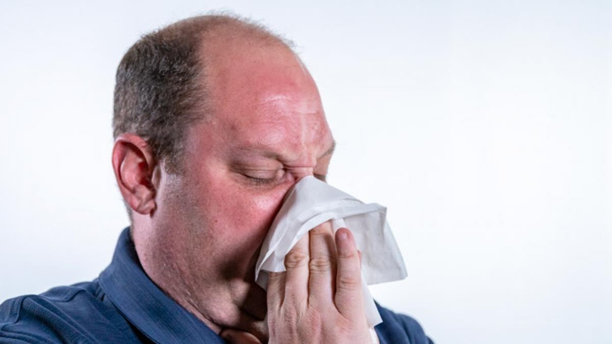 Image of man blowing is nose into tissue.