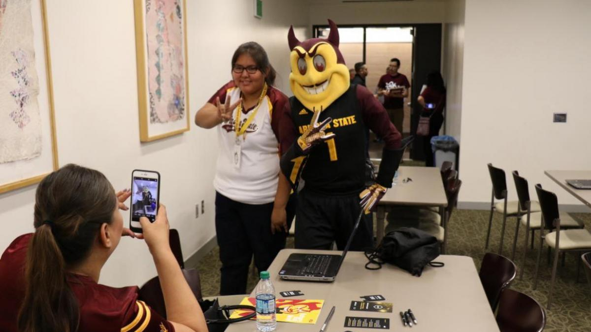 future female student posing for a selfie with Sparky the Sun Devil