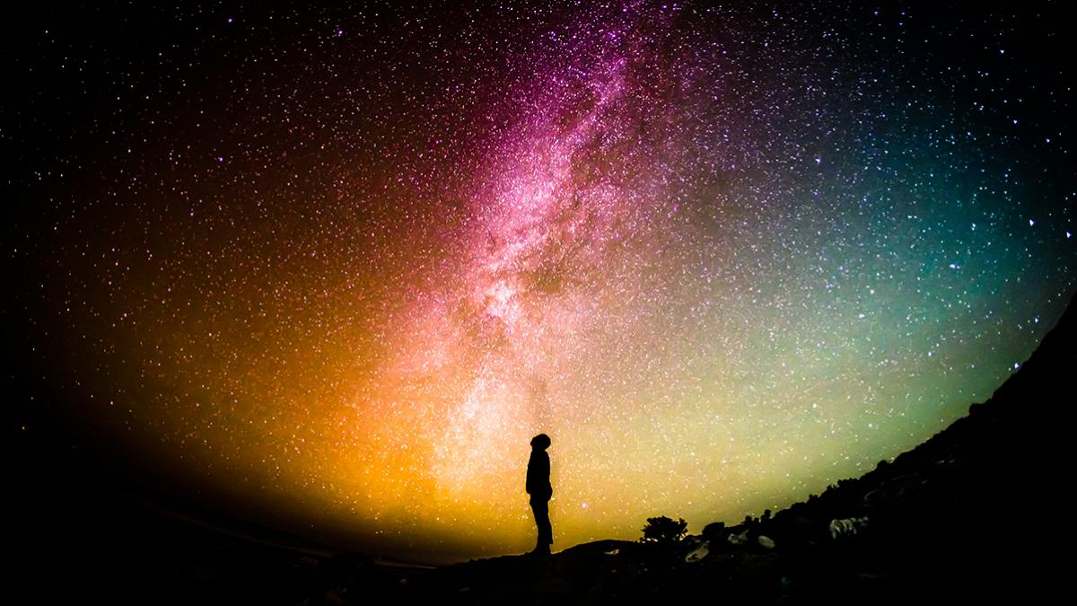 Silhouette of individual standing staring at colorful cosmic night sky