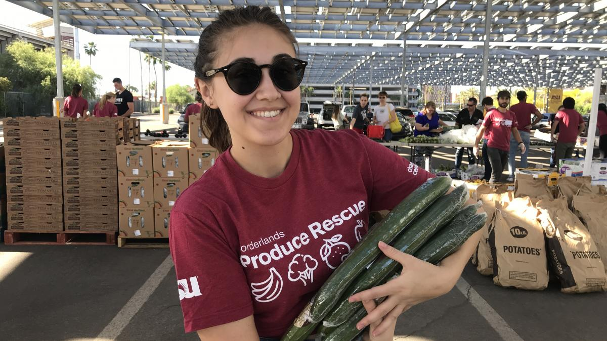 Photo of a person carrying cucumbers and wearing a maroon Borderlands Produce Rescue shirt