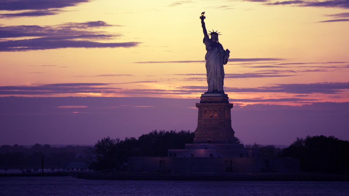The Statue of Liberty set against a deep purple sunset