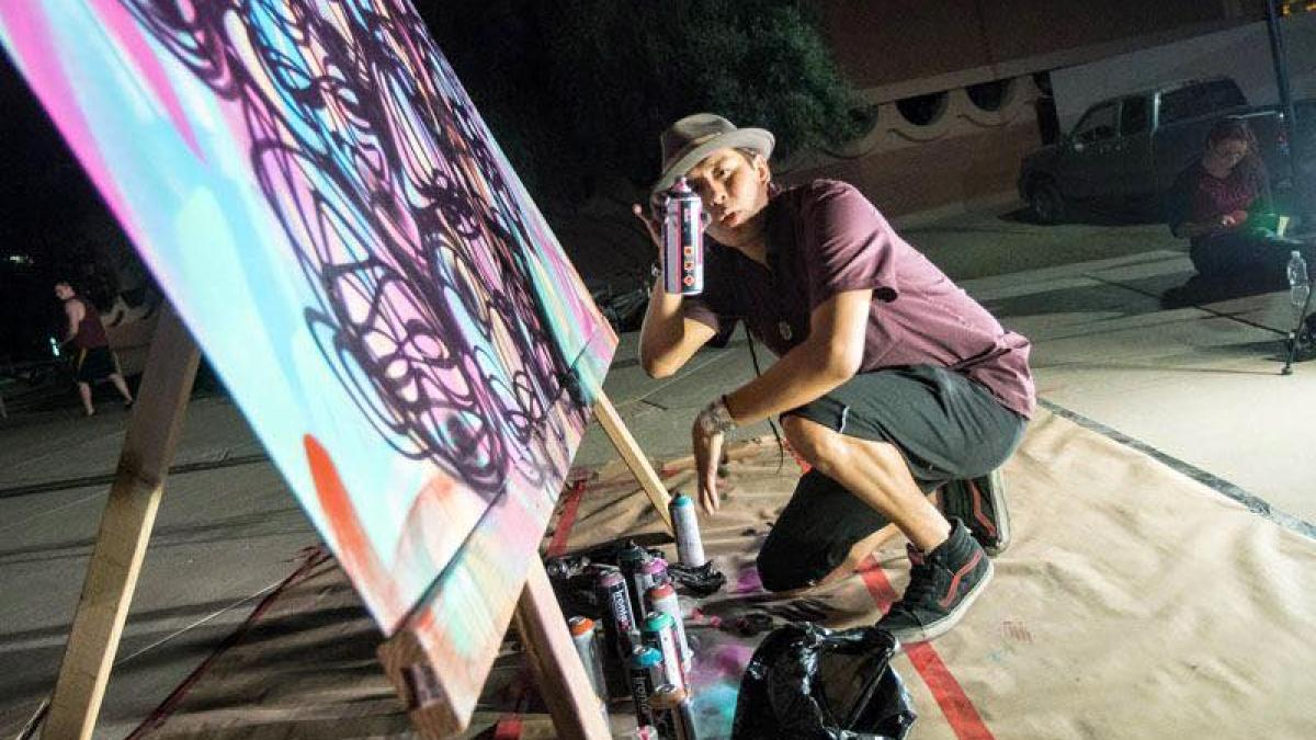man spray painting graffiti on a canvas