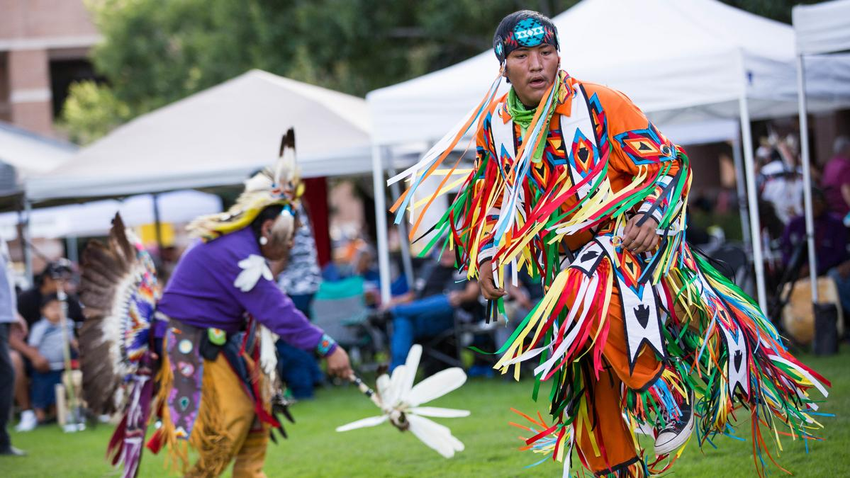 man in dancing in traditional Native American dress