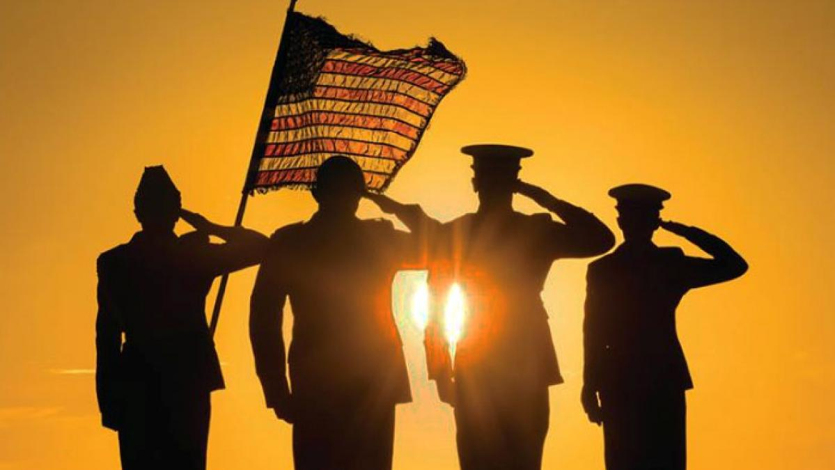 Military service members salute the United States flag with the golden sun behind them.