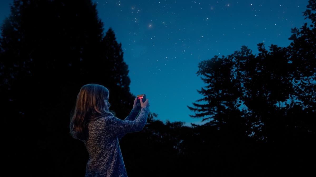 young girl holding up a device to collect data from the night sky
