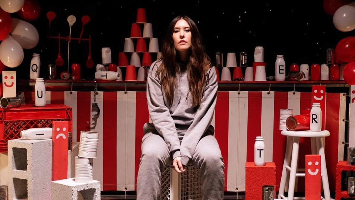 Sydney Sprague sits in a room of red cups, red and white banners