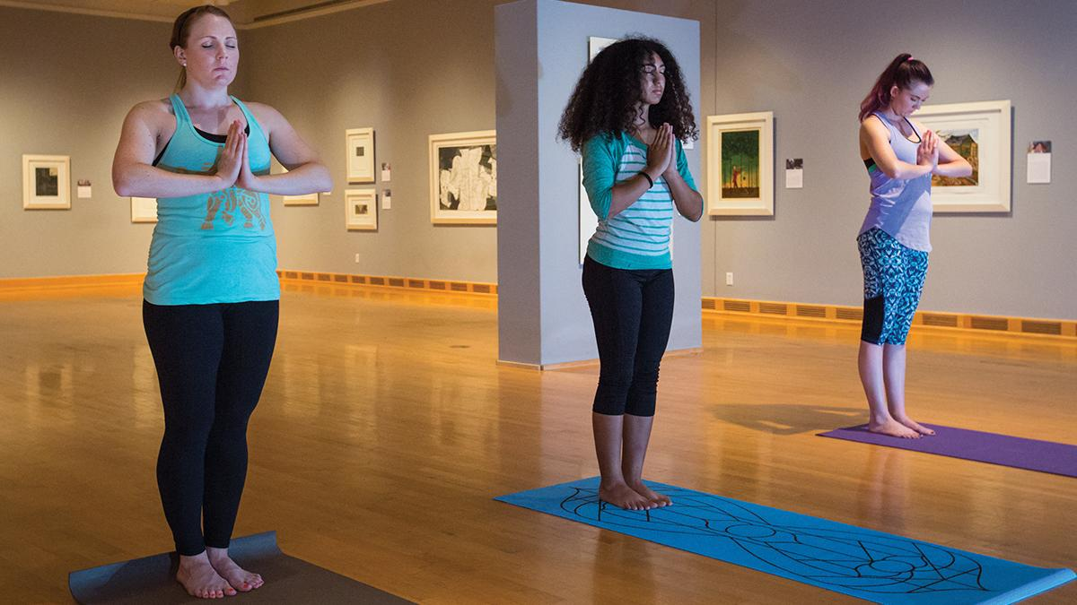 Three female students standing side by side in a yoga meditation pose.